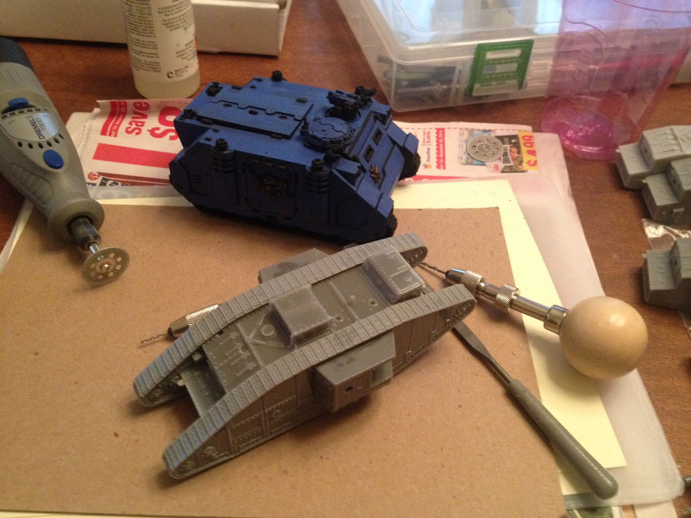 "Here is a size comparison between the bog standard British Mk V (dry fit pieces with none of the weapons and bitz added) and a bog standard Rhino Mk IIc (primed and basecoated only). You can just make out an ad in the newspaper imploring you to save $x. It probably says ""Save $8,"" but I like to believe that hidden '8' is really a '0' and it says, ""Save $0,"" which would be true whether you purchase the whatsit or not."